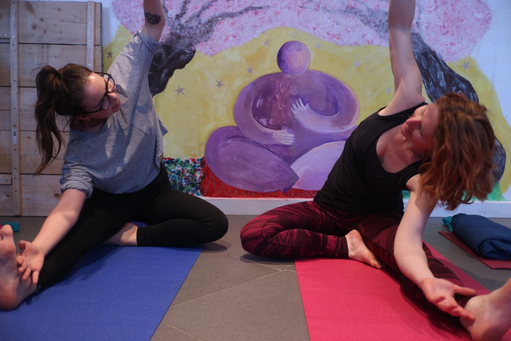 Two people sit in a yoga pose, facing each other
