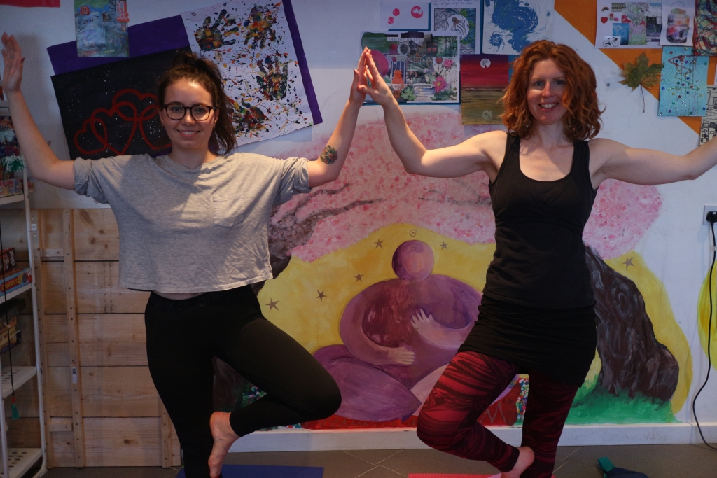 Two people stand in a yoga pose, facing the camera, pressing their hands together.